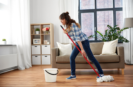 Foto de Happy Asian woman with mop cleaning floor at home - Imagen libre de derechos