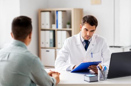 Photo pour Doctor with clipboard and male patient at hospital - image libre de droit