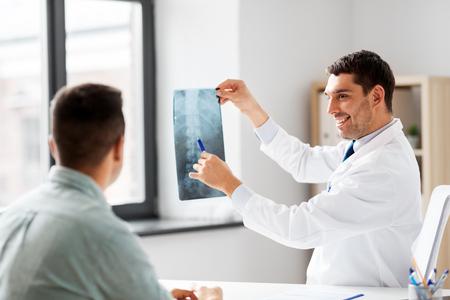 Photo pour Doctor showing x-ray to patient at hospital - image libre de droit