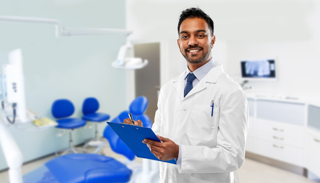 Photo pour medicine, dentistry and healthcare concept - smiling indian male dentist in white coat with clipboard over dental clinic office background - image libre de droit