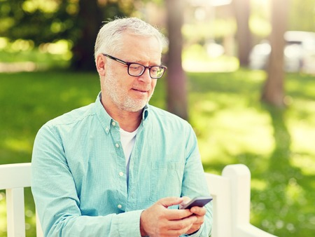 Photo pour technology, senior people, lifestyle and communication concept - happy old man dialing phone number and texting on smartphone at summer park - image libre de droit