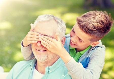 Photo pour family, generation and people concept - happy grandfather and grandson playing guess who game at summer park - image libre de droit