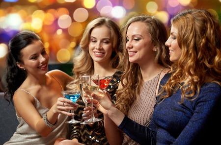 Photo pour celebration, bachelorette party and holidays concept - happy women or female friends clinking glasses at night club - image libre de droit