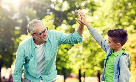 Photo pour old man and boy making high five at summer park - image libre de droit