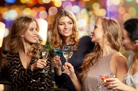 Photo pour happy women clinking glasses at night club - image libre de droit
