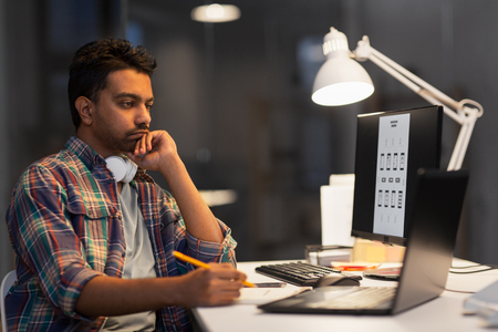 Foto de creative man with laptop working at night office - Imagen libre de derechos