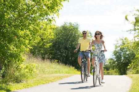 Photo pour happy young couple riding bicycles in summer - image libre de droit