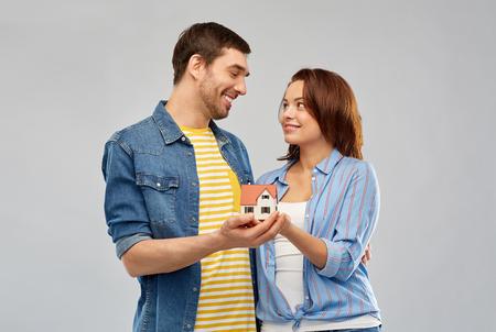 Photo pour smiling couple holding house model - image libre de droit