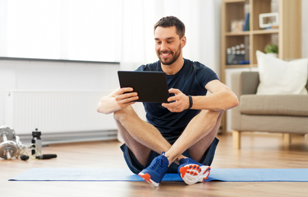 Photo pour Man with tablet computer on exercise mat at home - image libre de droit