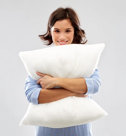 Foto de happy young woman in pajama hugging pillow - Imagen libre de derechos