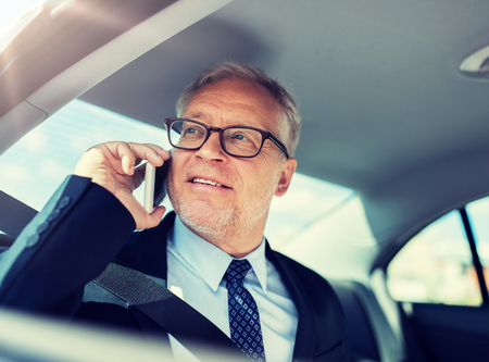 Foto de senior businessman calling on smartphone in car - Imagen libre de derechos