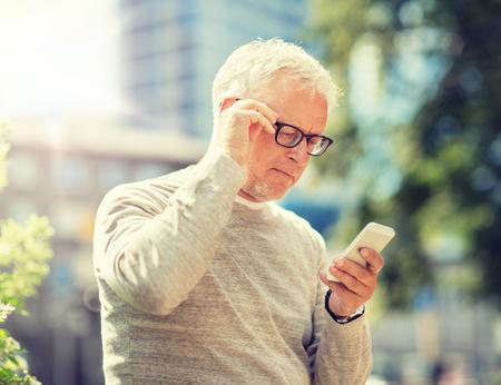 Photo pour senior man texting message on smartphone in city - image libre de droit