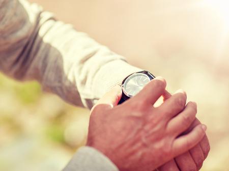 Photo pour senior man checking time on wristwatch outdoors - image libre de droit