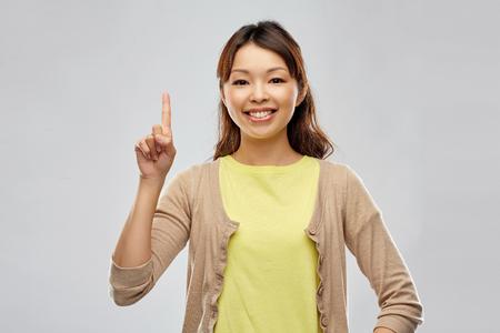 Foto für happy asian woman pointing finger up - Lizenzfreies Bild