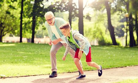 Photo pour grandfather and grandson racing at summer park - image libre de droit