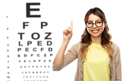 Foto de woman in glasses with finger up over eye chart - Imagen libre de derechos