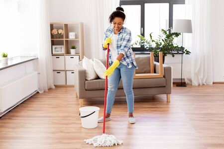 Photo pour african woman or housewife cleaning floor at home - image libre de droit