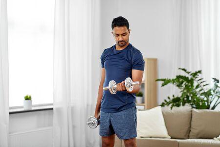 Photo pour indian man exercising with dumbbells at home - image libre de droit