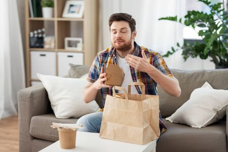 Photo pour smiling man unpacking takeaway food at home - image libre de droit