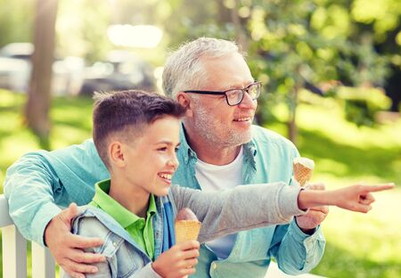 Photo pour family, generation, communication and people concept - happy grandfather and grandson eating ice cream at summer park - image libre de droit