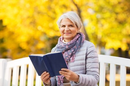 Photo pour old age, retirement and people concept - happy senior woman sitting on bench and reading book at autumn park - image libre de droit