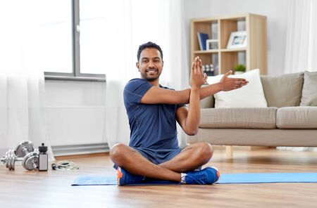 Foto de sport, fitness and healthy lifestyle concept - indian man training and stretching arm at home - Imagen libre de derechos