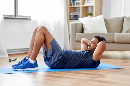 sport, fitness and healthy lifestyle concept - indian man making abdominal exercises at home