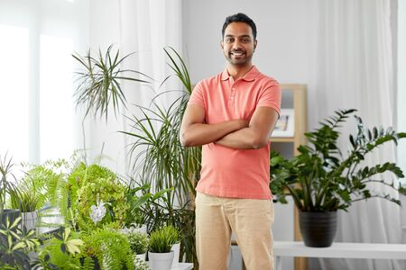 Photo for smiling indian man with houseplants at home - Royalty Free Image