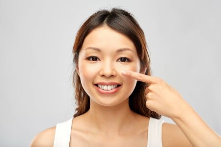 Photo pour Beauty and people concept - happy smiling young Asian woman touching her face - image libre de droit