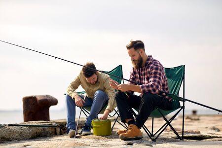 Photo pour Friends adjusting fishing rods with bait on pier - image libre de droit