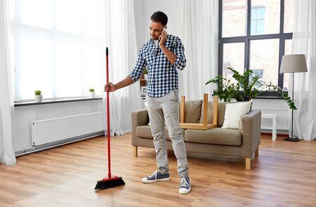 Photo pour Man with broom cleaning and calling on smartphone - image libre de droit