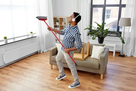 Photo pour Man with broom cleaning and having fun at home - image libre de droit