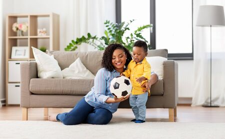 Foto de mother and baby playing with soccer ball at home - Imagen libre de derechos