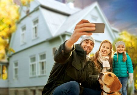 Photo pour family with dog taking selfie over house in autumn - image libre de droit