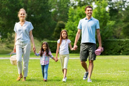 Foto de family with picnic basket walking in summer park - Imagen libre de derechos