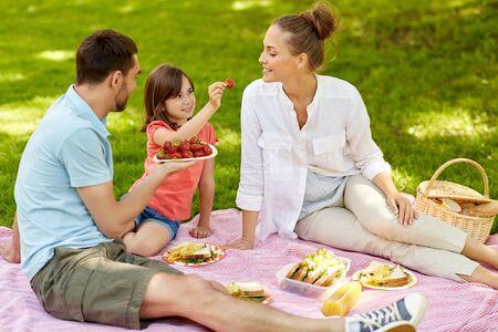 Foto de Family eating strawberries on picnic at park - Imagen libre de derechos