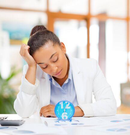 Photo pour tired businesswoman with alarm clock at office - image libre de droit