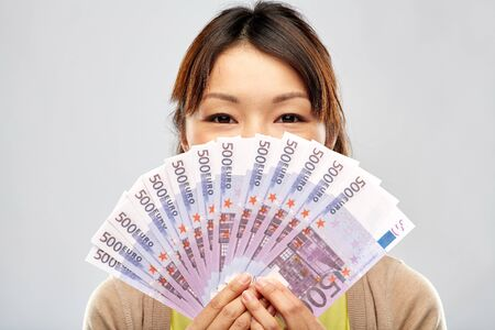 Photo pour People, ethnicity and portrait concept - Happy Asian young woman holding hundreds of euro money banknotes over grey background - image libre de droit