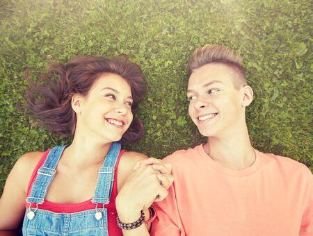Photo pour happy teenage couple lying on grass at summer - image libre de droit