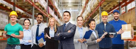Photo pour logistic business, delivery service and people concept - happy international team of employees over warehouse background - image libre de droit
