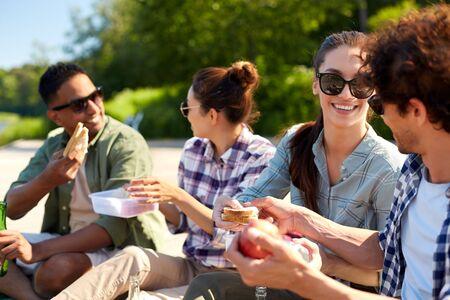 Photo pour happy friends having picnic on lake pier in summer - image libre de droit