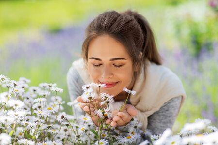 Foto de close up of woman smelling chamomile flowers - Imagen libre de derechos