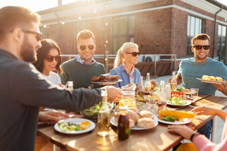 Photo pour happy friends eating at barbecue party on rooftop - image libre de droit