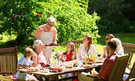 Photo pour family having dinner or barbecue at summer garden - image libre de droit
