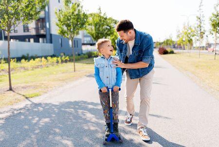 Foto de happy father and little son riding scooter in city - Imagen libre de derechos