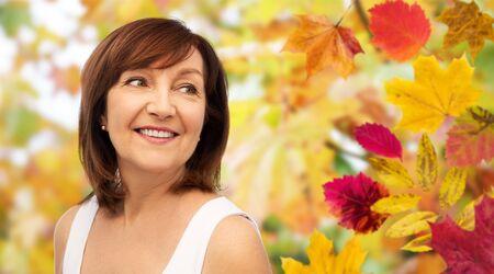 Photo pour portrait of happy senior woman over autumn leaves - image libre de droit