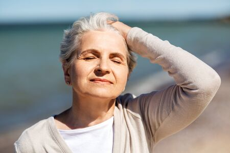 Foto per portrait of senior woman enjoying sun on beach - Immagine Royalty Free