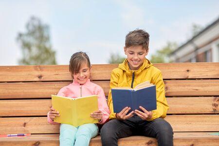 Photo pour school children reading books sitting on bench - image libre de droit