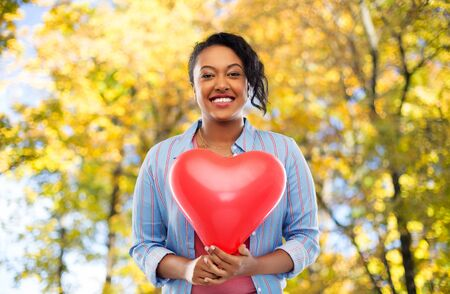 Photo pour african american woman with heart-shaped balloon - image libre de droit