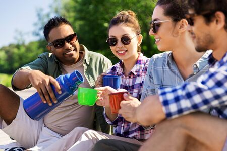Photo pour happy friends drinking tea from flask in summer - image libre de droit